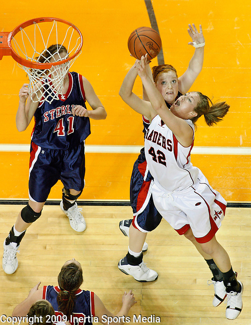 SIOUX CITY, IA - MARCH 13, 2009 --  Randa Hulstein #42 of Northwestern College (IA) shoots past Britany Gasper #34 of Sterling College during their game at the 2009 NAIA DII Women's Basketball National Championship at the Tyson Events Center. At left is Cathryn Wiebe #41 of Sterling. (Photo by Dick Carlson/Inertia)
