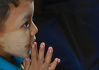 Young Boy praying at the Maha Muni during Full Moon Festival, Mandalay,  Myanmar, Burma,