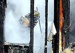 East Hartford Firefighter John Ozkowski is shrouded in smoke as he pulls floor boards in the burned out room at a home at 52 Garden Grove Road in Manchester while assisting Manchester Fire-Rescue-EMS at a second alarm fire that heavily damaged the single story dwelling, Wednesday afternoon, April 7, 2010, in Manchester. (Jim Michaud/Journal Inquirer)