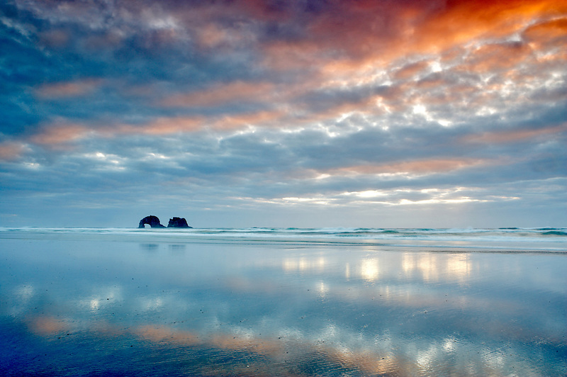 Low tide reflection with sunset and arch. Rockaway Beach. Oregon