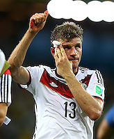 Thomas Muller of Germany applies pressure to a cut he suffered on the final whistle