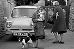 Upper Slaughter, Gloucestershire 1975 UK.<br /> <br /> Mr Harvey in the car and is Mrs Harvey.Mrs Rowlands carrying bottles outside the church gates.