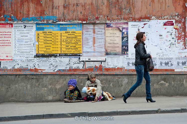 A Roma woman with two children begs in a street in central Tbilisi, Georgia.