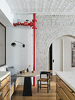 In the breakfast nook, a custom Hollis+Morris table is illuminated by a José Esteves-designed sconce from Interieurs. The sprinkler pipe, painted in FDNY-approved Benjamin Moore Vermilion, pops against the loft's token brick archways, which were whitewashed in Farrow & Ball's Ammonite for a fresh feel.