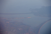 A nice view of the promontory of the Argentario in Toscana, from an airplane between Paris and Rome. The stretches of land of the tombolo of Giannella and the tombolo of Feniglia are clearly visible, but the panorama is centered on the promontory of Orbetello, and the thin line of its bridge, beautifully shining in the sunset light.