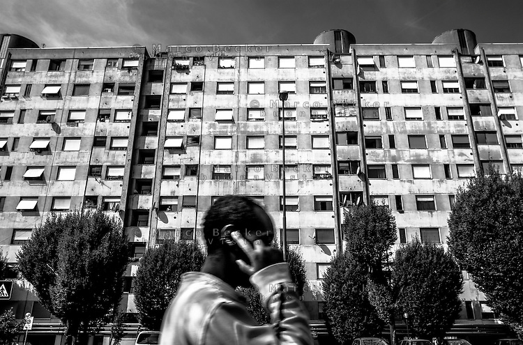 Milano, un ragazzo africano passa davanti alle case popolari al quartiere Salomone (La Trecca), periferia est --- Milan, an African man passing in front of public housing at Salomone district (La Trecca), east periphery