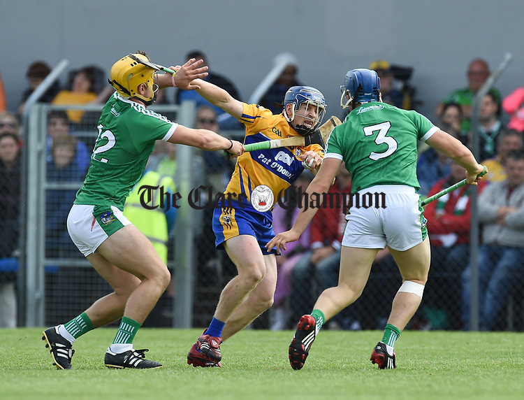 Podge Collins of Clare in action against Tom Morrissey and Mike Casey of Limerick during their Munster championship game in Ennis. Photograph by John Kelly.