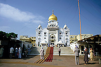 People standing outside a Sikh temple with a golden dome, Delhi, India.