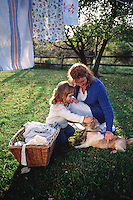Mother and daughter hanging laundry and plying with pet puppy outdoors..
