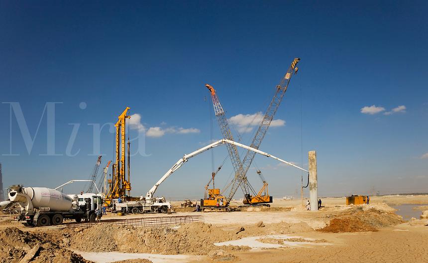Dubai.  New construction site with piling rigs, concrete pump, cranes and ready mixed concrete trucks..