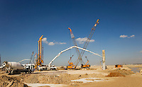 Dubai.  New construction site with piling rigs, concrete pump, cranes and ready mixed concrete trucks..