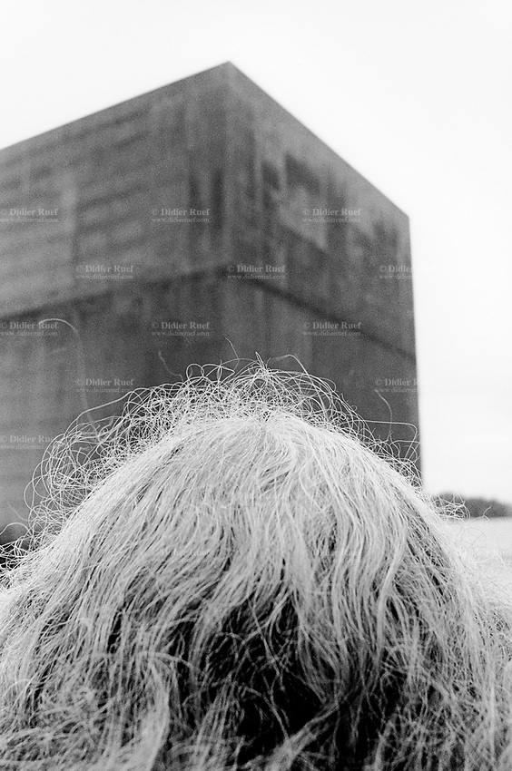 """Switzerland. Fribourg canton. Morat - Murten. Arteplage, Expo 02. Woman's long hair in front of """"The Monolith"""" by the architect Jean Nouvel. A three-storey-high rusting steel cube anchored a few hundred metres off shore.The rust symbolises the passing of time in a town, which appears trapped in its past, and the sheer size of the structure means this past cannot be overlooked. National exhibition. © 2002 Didier Ruef.."""