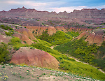 Badlands National Park, SD  <br /> Banded pastel colored hills and cliffs with grass covered washes near Dillon Pass