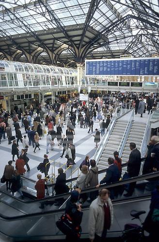 London, England. Crowd of people on Liverpool Street station; escalators; signs.