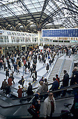 London, England. Crowd of people on Liverpool Street station; escalators; signs.