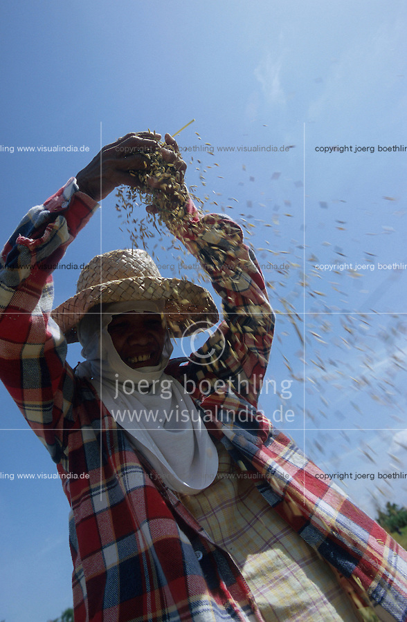 PHILIPPINES, Negros, woman with straw hat winnowing rice to separate grain from chaff / Philippinen, Negros, Frau mit Strohhut trennt die Spreu vom Reiskorn mit Hilfe des Windes
