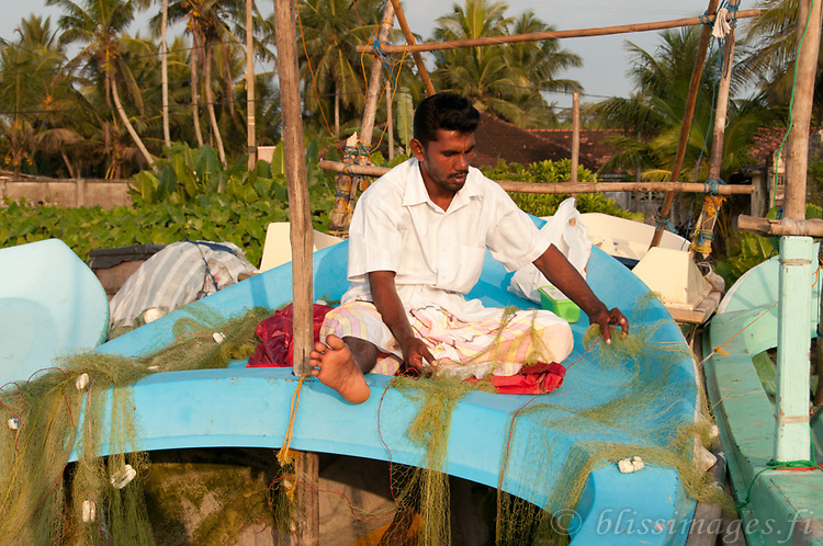 Fisherman repairing his nets at Beruwala, Sri Lanka