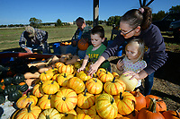 Rebekah Hodges helps her children Silas Hodges, 4, and Abigail Hodges, 2, as they pick out pumpkins Tuesday, Oct. 12, 2021, as Bill Yoes (from left) and Fred Collins clean up pumpkins at Collins' stand in Prairie Grove. This is the final year for Collins to sell pumpkins and squash after 30 years of growing and selling. His stand is open through Thanksgiving. Visit nwaonline.com/211013Daily/ for today's photo gallery.<br /> (NWA Democrat-Gazette/Andy Shupe)