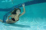 Young teenage girl in pool, black bikini, long brownish hair, gold necklace, sheer turquoise scarf, underwater photography, underwater Model.Alexa Smith MR