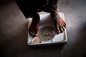 A young woman is weighed at the Anganwadi centre in Kalesra Kala village in Lalitpur district of Uttar Pradesh, India. The Indian government spends $1.4 billion a year - on programs that include weighing newborn babies, counseling mothers on healthy eating and supplementing meals, but none of this is yeilding results. According to UNICEF, some 48% of Indian children, or 61 million kids, remain malnourished, the clinical condition of being so undernourished that their physical and mental growth are stunted. Photo: Sanjit Das/Panos for The Wall Street Journal.Slug: IMALNUT