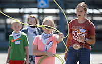 Adrianna Parsons, the top hand and member of the Rodeo of the Ozarks Rounders, teaches Quinnley Roeder, 9, how to throw a lasso Thursday, June 3, 2021, during the first day of the Rodeo of the Ozarks Horse Camp at Parsons Stadium in Springdale. The two day camp, staffed by volunteer Rounders, is for ages 6 to 12 and emphasizes equine basics that include safety, anatomy of a saddle, riding a horse and other fun activities. Check out nwaonline.com/210604Daily/ and nwadg.com/photos for a photo gallery.<br /> (NWA Democrat-Gazette/David Gottschalk)