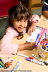 Education Preschool 3-4 year olds portrait of girl smiling looking up from her work vertical