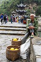 Zhenyuan, Guizhou, China.  Pomelo Vendor Sitting on Wall of Zhusheng Bridge across the Wuyang River.