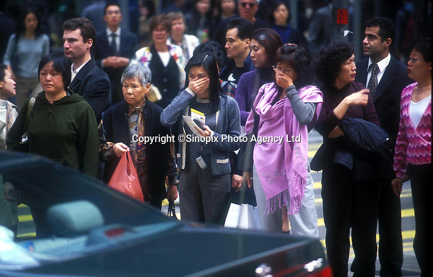 Two women cover their mouth and nose while a car pass by. Since Hong Kong is a very crowded ctiy, pollution are getting worse by time.