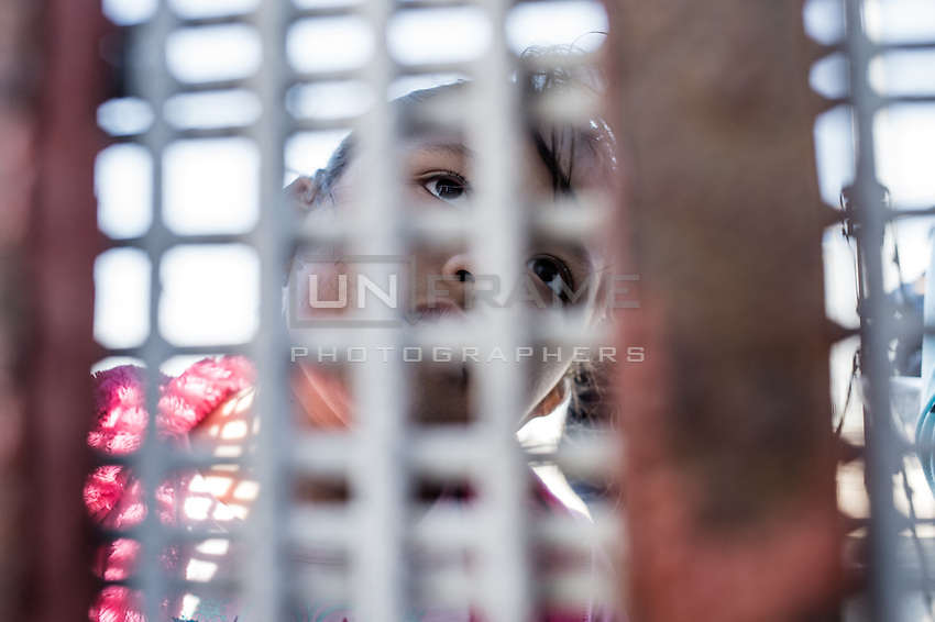 Child placed in a foster family in the US is looking through the border fence at her mother deported to tijuana.  Tijuana, Mexico. Jan 04, 2015.