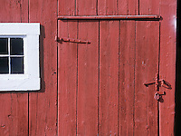 Detail of old weathered red barn with white window. White Mountains, New Hampshire.