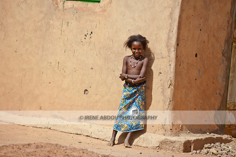 A Fulani girl stands against a mud house in the town of Djibo in northern Burkina Faso.