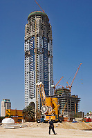 Tall residential tower block under construction with piling work in the foreground.   Dubai. United Arab Emirates.