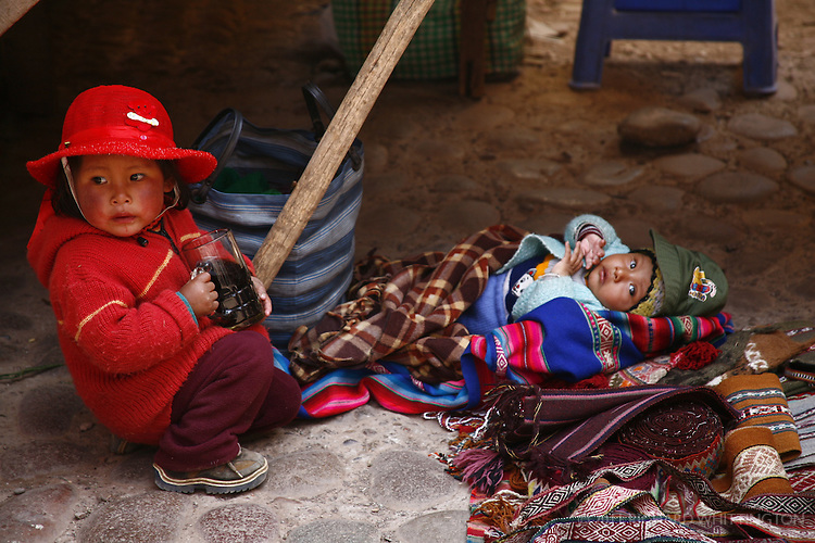 Two young Peruvian children sitting in the streets of Pisac.