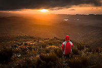 Hiker looking towards Mangarakau wetlands in background at sunset, Nelson Region, South Island, New Zealand