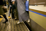 A woman in traditional Japanese dress exits train car, train station, Tokyo, Honshu, Japan