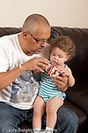 13 month old baby girl at home with father who is her primary caregiver shown how to turn crank on musical toy new toy father turning crank with her hand on it underneath vertical