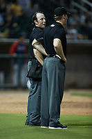 Home plate umpire Austin Jones (left) chats with first base umpire Reed Basner between innings of the game between the Mississippi Braves and the Birmingham Barons at Regions Field on August 3, 2021, in Birmingham, Alabama. (Brian Westerholt/Four Seam Images)