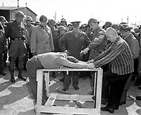 Gen. Dwight D. Eisenhower watches grimly while occupants of a German concentration camp at Gotha demonstrate how they were tortured by the Nazi sadists operating the camp.  Generals Bradley and Patton are at his right.  Germany, April 12, 1945.  Lt. Moore.  (Army)<br /> NARA FILE #:  111-SC-203475<br /> WAR & CONFLICT BOOK #:  1113