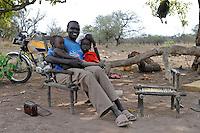 SOUTH-SUDAN Rumbek , village, Colocok, Dinka man with children sitting on wooden chair listen to radio / SUED SUDAN, Rumbek,  Dorf Colocok, Dinka Mann sitzt mit Kindern auf Holzsessel