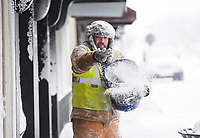 Bentonville Public Works crew member Eric Hersha spreads calcium chloride pellets, Monday, February 15, 2021 along the sidewalks on Main Street near the Square in Bentonville. The pellets help melt the snow. Check out nwaonline.com/210216Daily/ for today's photo gallery. <br /> (NWA Democrat-Gazette/Charlie Kaijo)