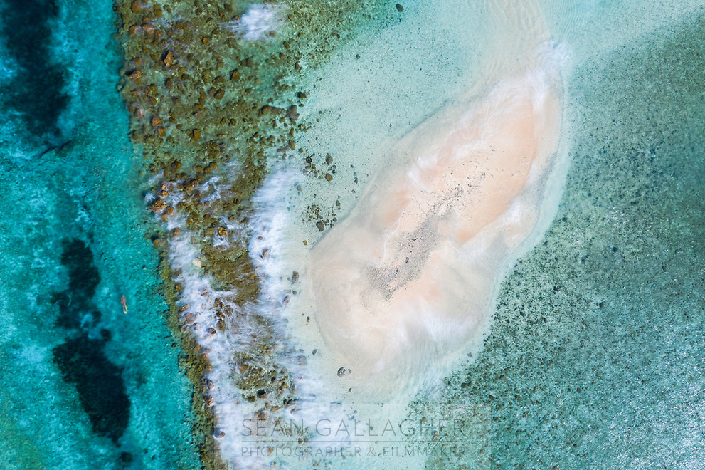 """Seen from above, it's easy to see why the Southwest Pacific country of Tuvalu has been identified as one of the world's most vulnerable nations to climate change. The country is made up of a collection of small islands and coral atolls, totalling only 27 square kilometres, scattered over 500,000 square kilometres of ocean. The highest point throughout the country is only 5 metres above sea level, resulting in special vulnerability to sea level rise. According to the Tuvaluan government, """"since 1993, sea level near Tuvalu has risen about 5mm per year; this is larger than the global average."""" Other challenges face the country including drought, ocean acidification and waste problems."""
