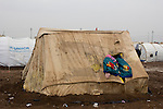 DOMIZ, IRAQ: Syrian refugee have used jackets to plug a hole in their tent in the Domiz refugee camp in the Kurdish region of northern Iraq...The semi-autonomous region of Iraqi Kurdistan has accepted around 60,000 refugees from war-torn Syria. Around 20,000 refugees live in the Domiz camp which sits 60 km from the Iraq-Syria border...Photo by Younes Mohammad/Metrography