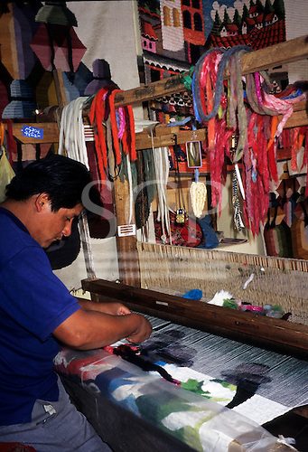 Ollantaytambo, Peru. Man using a traditional loom to make a decorative tapestry to sell to tourists.
