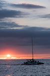 Kona, Big Island of Hawaii, Hawaii; sunset over the Pacific Ocean silhouettes a catamaran sail boat