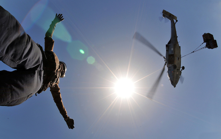 """080605-N-7981E-409 Arabian Gulf (June 5, 2008)- Aviation Structural Mechanic Airman Brian Thurman, a landing signalman enlisted (LSE) assigned to """"Golden Falcons"""" of Helicopter Anti-submarine Squadron (HS) 2, directs an MH-60S Knight Hawk assigned to """"Wildcards"""" of Helicopter Sea Combat Squadron (HSC) 23 as it delivers stores on the flight deck of Nimitz-class aircraft carrier USS Abraham Lincoln (CVN 72) during a vertical replenishment at sea with Fast Combat Support Ship USNS Rainer (T-AOE 7). Lincoln is deployed to the U.S. Navy 5th Fleet area of responsibility to support Maritime Security Operations (MSO).  MSO help develop security in the maritime environment, which promotes stability and global prosperity.  These operations complement the counterterrorism and security efforts of regional nations and seek to disrupt violent extremists' use of the maritime environment as a venue for attack or to transport personnel, weapons or other material.  U.S. Navy photo by Mass Communications Specialist 2nd Class James R. Evans (RELEASED)"""