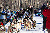 Kristy Berington and team run past spectators on the bike/ski trail during the Anchorage ceremonial start during the 2014 Iditarod race.<br /> Photo by Britt Coon/IditarodPhotos.com
