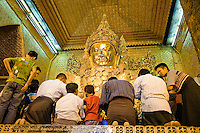 Myanmar, Burma.  Mandalay.  Mahamuni Buddhist Temple.  Men and boys apply gold leaf to Buddha statue.  Only males are allowed to approach the Mahamuni Buddha.