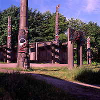 Haida Totem Poles and Plank House at Museum of Anthropology, University of British Columbia (UBC), Vancouver, BC, British Columbia, Canada.  Memorial Pole (left midground) and Haida Mortuary House.