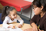 Education Childcare 3 year olds start of day sign-n routine girl smiling up at female teacher who is talking to her