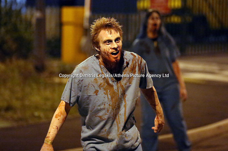 Pictured: In the final kill, Zombies chase after players in a Cardiff street. Saturday 29 March 2014<br /> Re: Cardiff thrill-seekers were chased around the city last night by a horde of terrifying zombies as part of virtual apocalypse game 2.8 Hours Later.<br /> Starting in Grangetown, groups of zombie-enthusiasts walked, jogged, hid and run around a quarantined area of the city, which included Cardiff City Stadium and Ninian Park Primary School, to escape a deadly mass of infected undead.<br /> But it wasn't just zombies threatening to disturb the peace of the city – aggressive police and surveillance squads forcing people to stand up against walls and avoid their harmless friends for fear of spreading infection wreaked havoc in the quarantine.